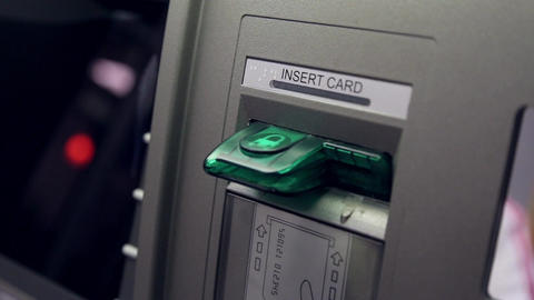 Detail of woman's hand inserting a bank card at an Footage