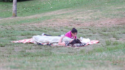 Mother and daughter lying down on the grass in the Footage