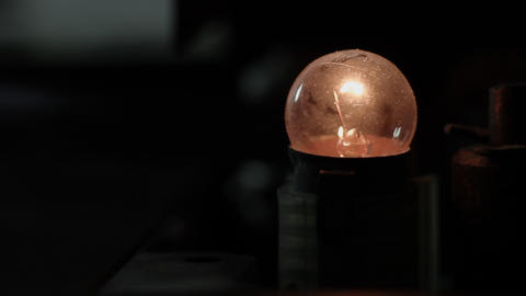 Ungraded: Small Light Bulb Flickering In Dark stock footage