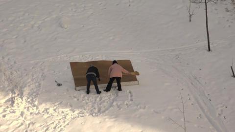 Women beaten out the carpet in the snow. 4K Footage