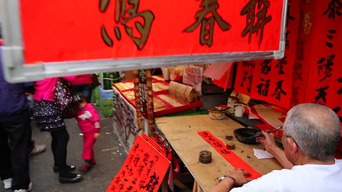 Man writing chinese at Chinese new year market Live Action