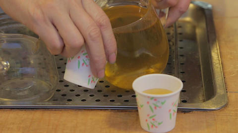 woman pouring Taiwan tea into paper cup Live Action