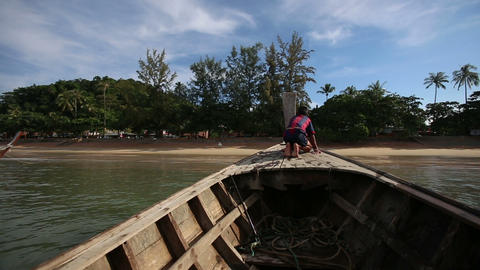 boy sits on longtail boat sailing out beach in tro Footage