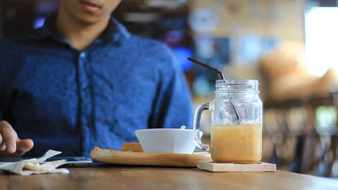 Young man with tablet computer drinking coffee in cafe Footage