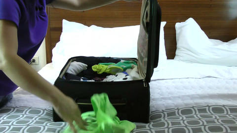 Businesswoman packing in suitcase in hotel room Footage