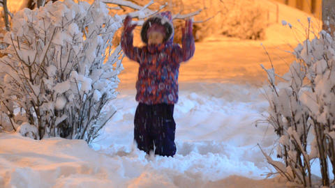 Happy beautiful little girl throws snow in winter, night lighting Footage