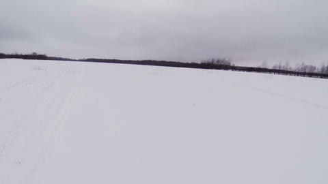 Snowmobile rides on winter field Footage