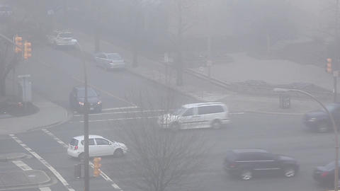 Top Shot Of Car Driving Through An Intersection With Heavy Fog stock footage