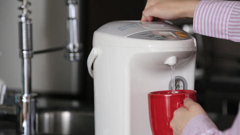 Business woman pushing hot water button on electric thermo pot for drinking coff Footage