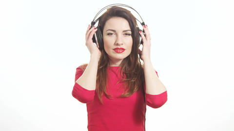 Attractive female in red t shirt dancing to the music in big headphones notices Footage
