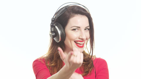Beautiful woman in red swinging to the music in big headphones flirting with the Footage