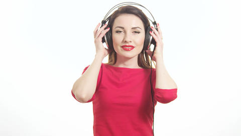 Cute woman in red listening to the music takes off big headphones and winking to Footage