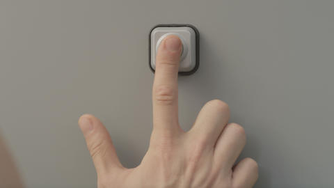 Closeup of male palm finger ringing grey door bell on sunny day Footage
