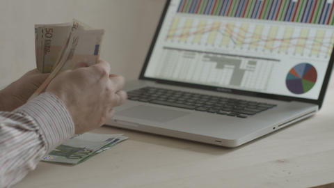 Businessman Counting Euro Bills In Front Of Notebook stock footage
