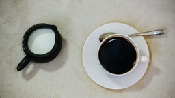 Espresso in white cup and saucer with spoon, milk in jar on grunge vintage backg Footage
