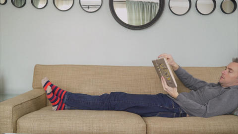 Man Reading Book in a Cozy Livingroom in 4K Live Action