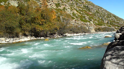 Blue River flows into the sunlit valley, autumn Footage