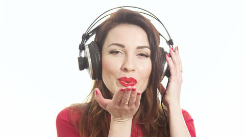 Attractive female in red t-shirt dancing to the music in big headphones notices Footage