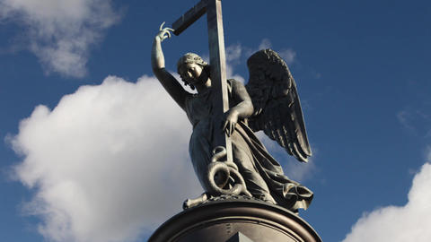 statue of winged angel with cross in blue sky Live Action