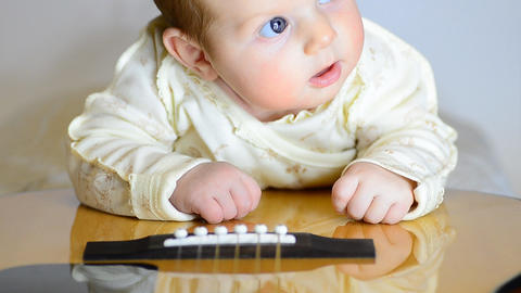Newborn Baby Lying on Guitar. Motorized Dolly Shot Footage