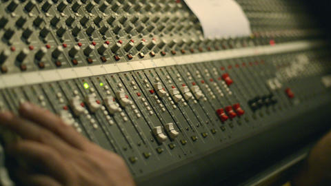 Analog audio mixing board with several channels and push buttons visible Footage