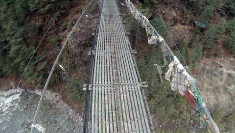 HIMALAYAS, NEPAL - MARCH, 2014: 2.7. Tourists walk on a suspension bridge in the Footage
