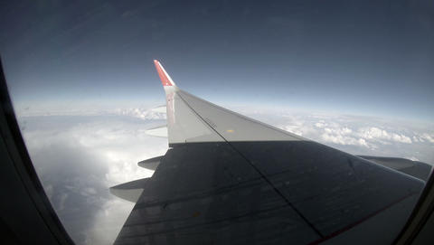 2.7K. Airplane wing out of window on blue sky background, Full HD. 2704x1524 Footage