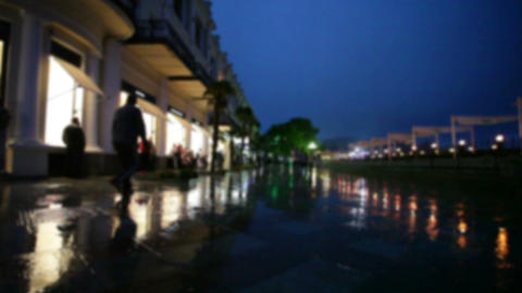 People go in rain on embankment in seaside southern city in summer evening Footage