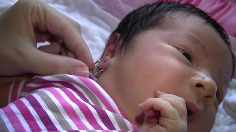 Mother arranges gold earrings of Newborns 01 Footage