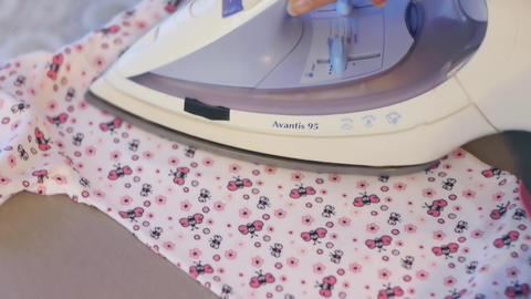 Woman ironing children s clothing 05 Footage