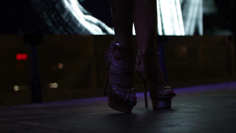 A close up of high heel shoes of the strip dancers on the stage of nightclub Live Action