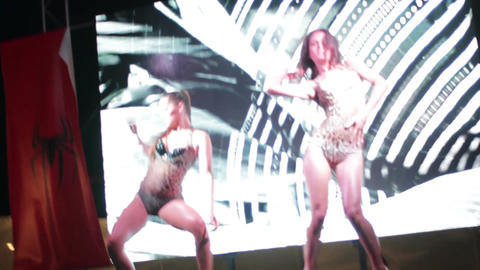 Two sexy strip dancers on the stage of summer nightclub Live Action