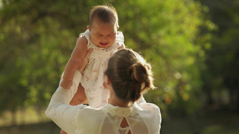 Mother Lifting Up And Turning Around Little Baby Daughter In Park stock footage
