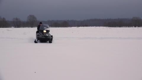 Snowmobile rides on winter field. 4K Footage