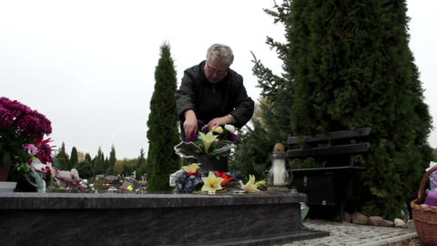 Woman adjusts flowers in a stone vase attached to tombstone Footage