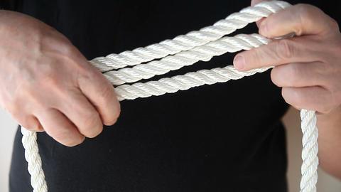 man ties sheepshank knot Stock Video Footage