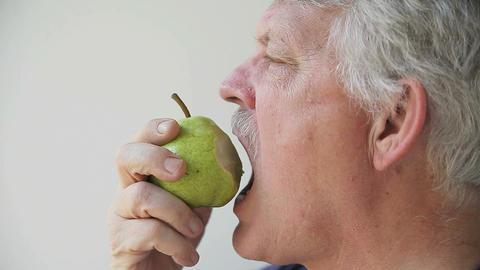 man eats pear Stock Video Footage