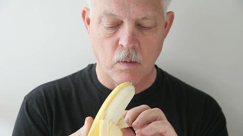 man peels and eats banana Stock Video Footage