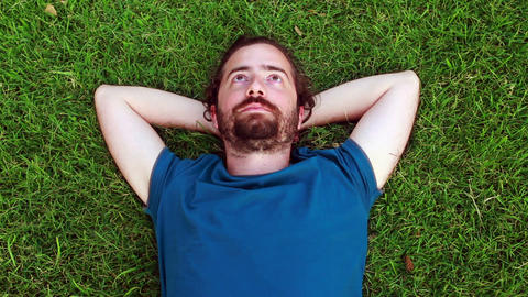 Young guy lie down on grass Stock Video Footage