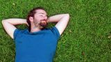 Young guy lie down on grass Footage