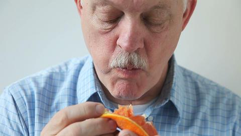 man eats section of orange Footage