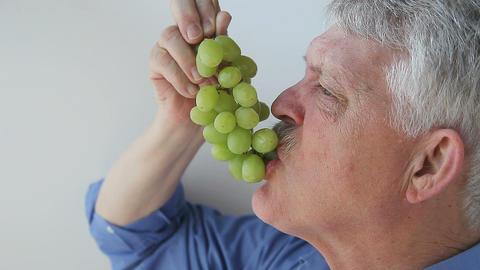 older man eats green grapes Footage