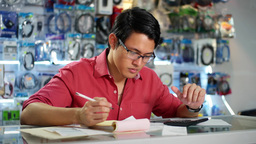 Chinese Man Working In Computer Shop Checking Bills And Invoices Footage