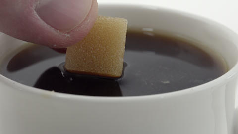 Sugar cube soaked in coffee. 4K UHD Footage