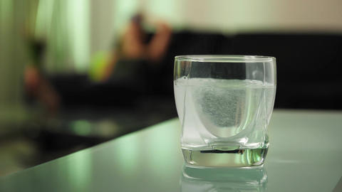 Sick Woman Puts Effervescent Tablet Aspirin In Glass Of Water stock footage