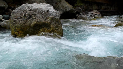 torrent clear blue water flowing among the rocks Footage