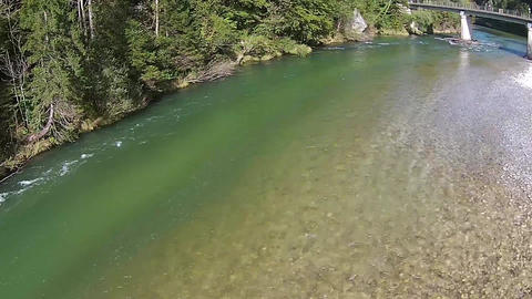 bridge over a river in the mountains in Austria, crystal clear water and stones  Footage