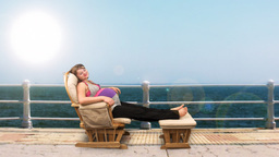 Pregnant woman on rocking chair at seaside Stock Video Footage