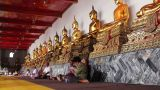 people sits under golden buddha statues Footage