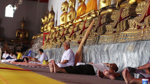 people sits under golden buddha statues Stock Video Footage
